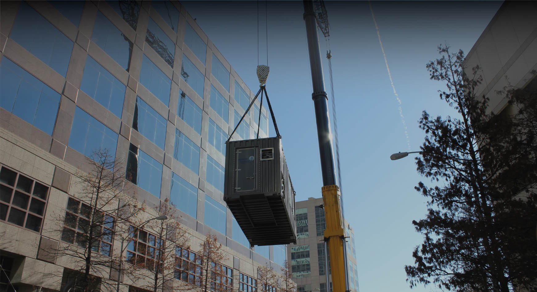 crane moving cargo container outside office building