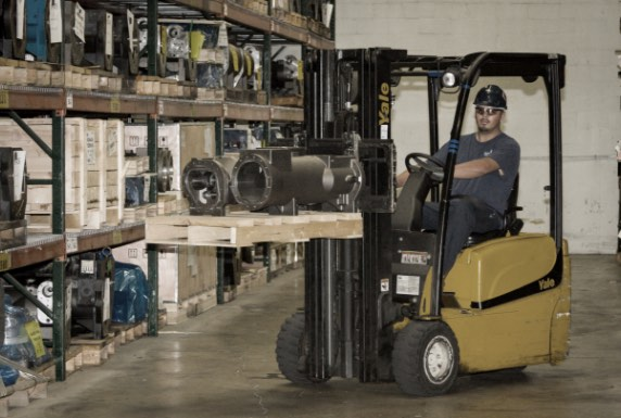 man moving equipment parts with forklift