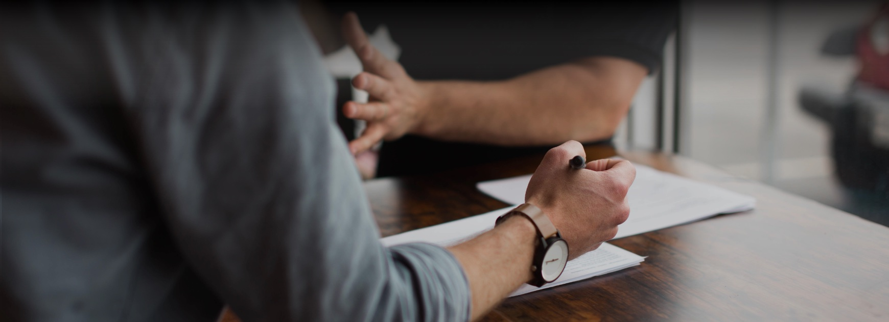man writing on paper while discussing with colleague